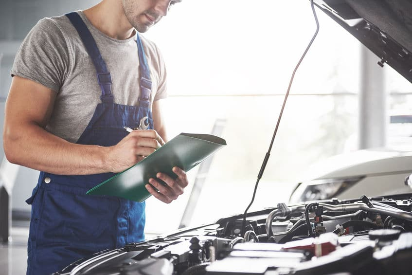 A photo of a mechanic checking the condition of a car engine prior to a road trip.