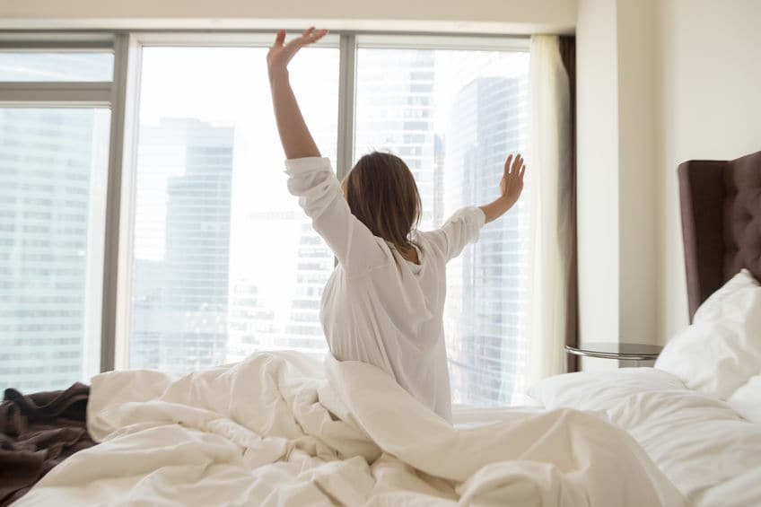 This photo shows a woman sitting up in bed, stretching her arms, after a refreshing night's sleep.