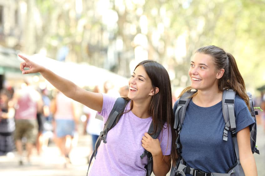 This photo shows two young ladies with backpacks on, as they explore a new city and don't get lost.