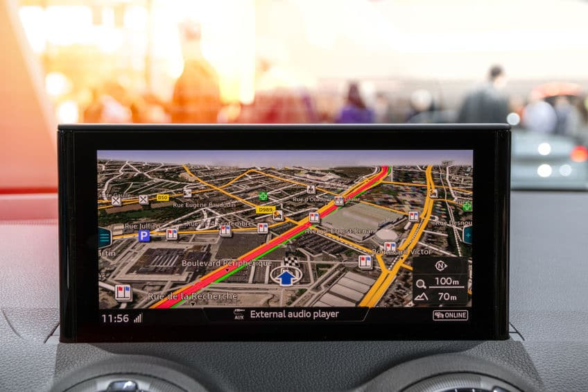 A photo of a stand alone GPS unit, mounted on a car dashboard, showing which route to drive.