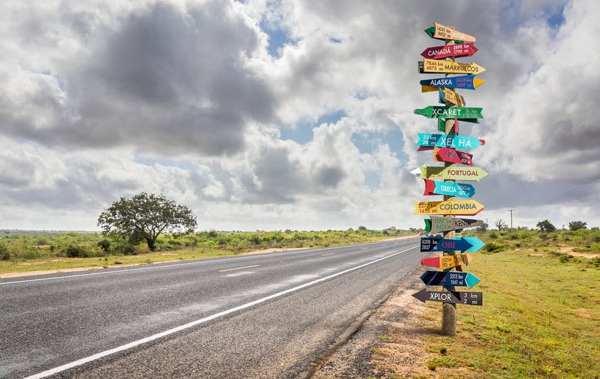 This is a photo of a sign post with 17 directional signs, symbolizing a long extended journey.