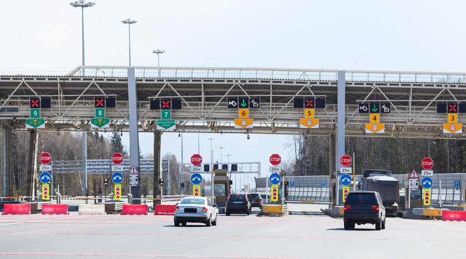 This photo shows multi lanes of cars coming to a stop because of toll booths on the road.