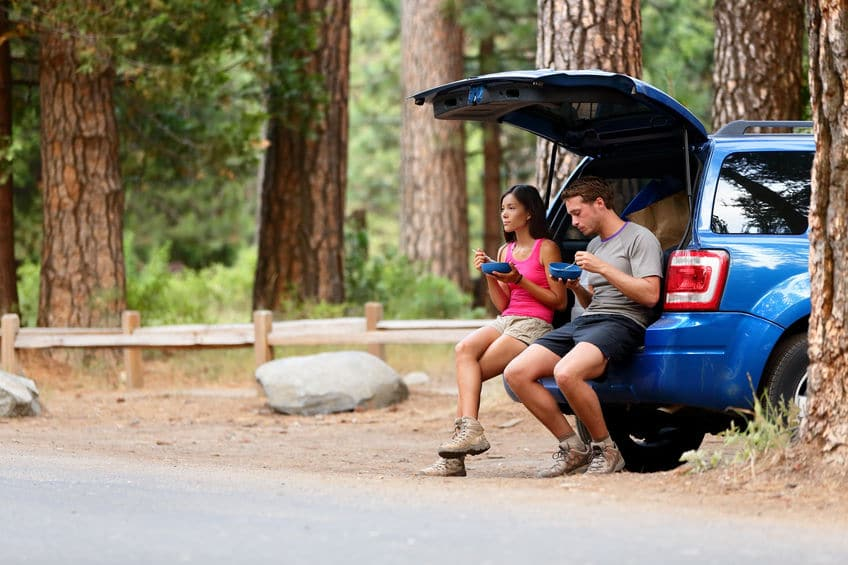 This photo shows a young couple in a forested rest stop, eating healthy food on their road trip.