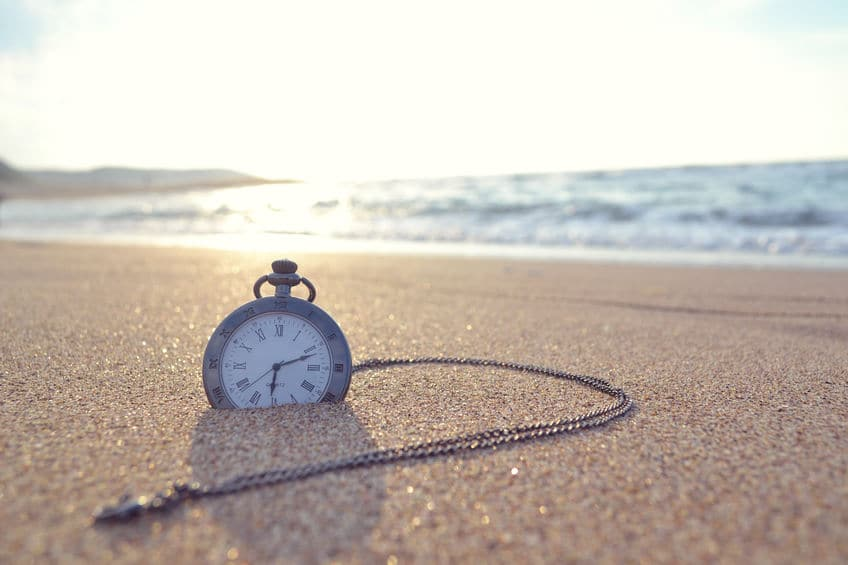 This photo shows an old pocket watch, half buried in sand, on an ocean shoreline, as a metaphor for a long term stay hotel.
