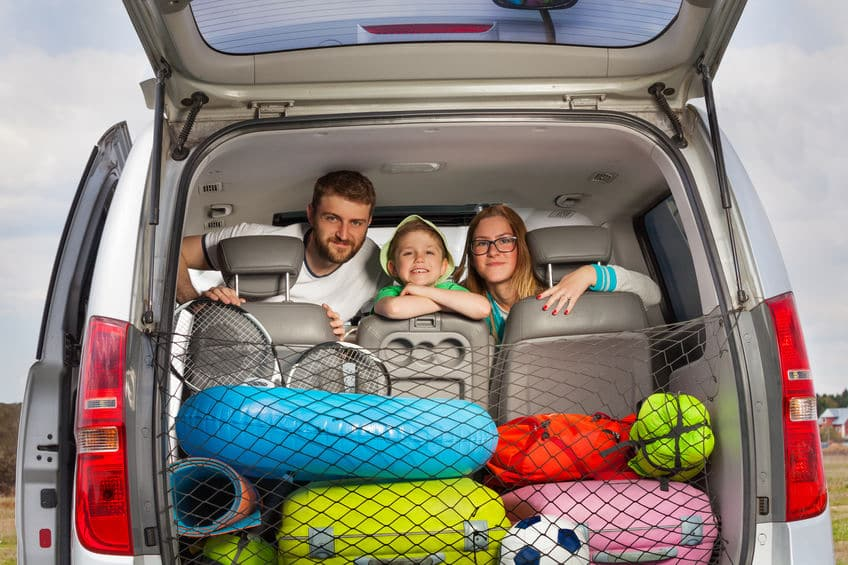This photo shows a family looking out the back of their fully packed SUV, ready for a road trip vacation.