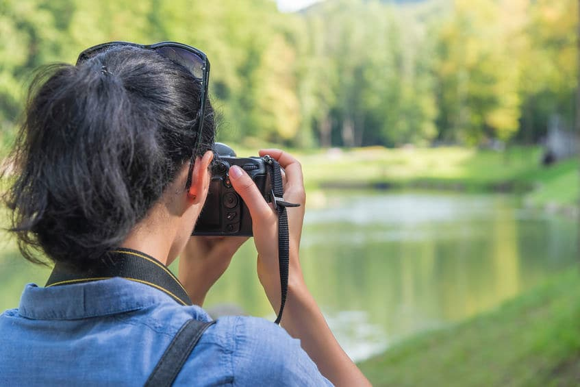 This photo shows a woman taking a photo of a beautiful lake scene with a digital SLR camera.