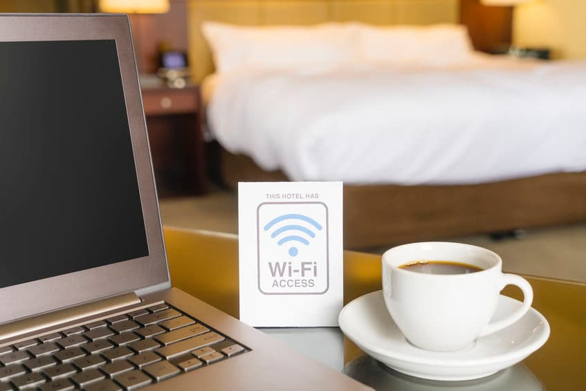 This photo shows a close up of a computer and a sign saying free wi-fi, with the bedroom out of focus in the background.