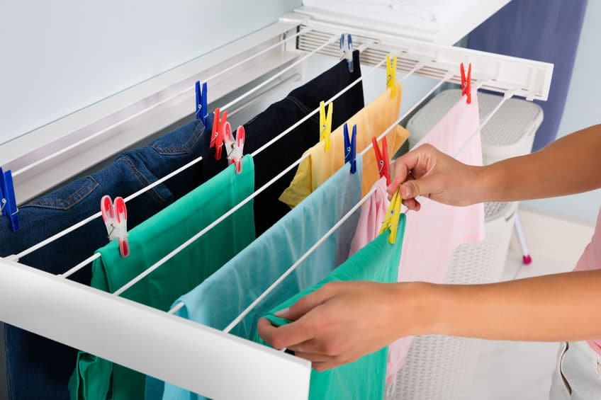 This photo shows freshly washed laundry being clipped onto a wall mounted drying rack.