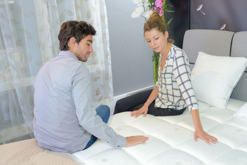 This photo shows a young couple inspecting the sofa bed mattress of a hotel room before accepting the reservation.