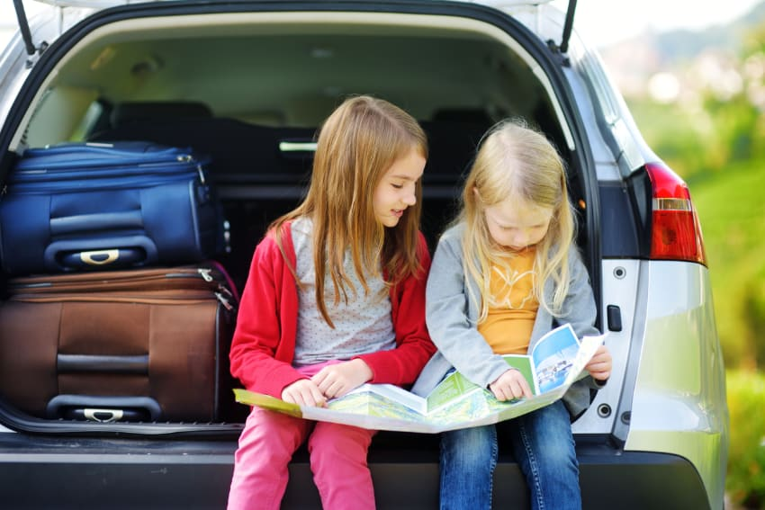 This photo shows two children sitting on the tailgate of a fully packed SUV, looking at a map, planning the route for a road trip vacation.