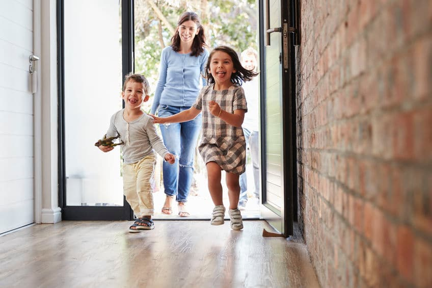 This photo shows two excited children running through a door, with their parents behind them, coming home after a road trip.