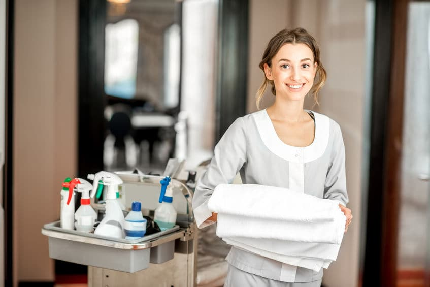 This photo shows a hotel housekeeping staff member with a cleaning cart and fresh towels, symbolizing clean and sanitary conditions.