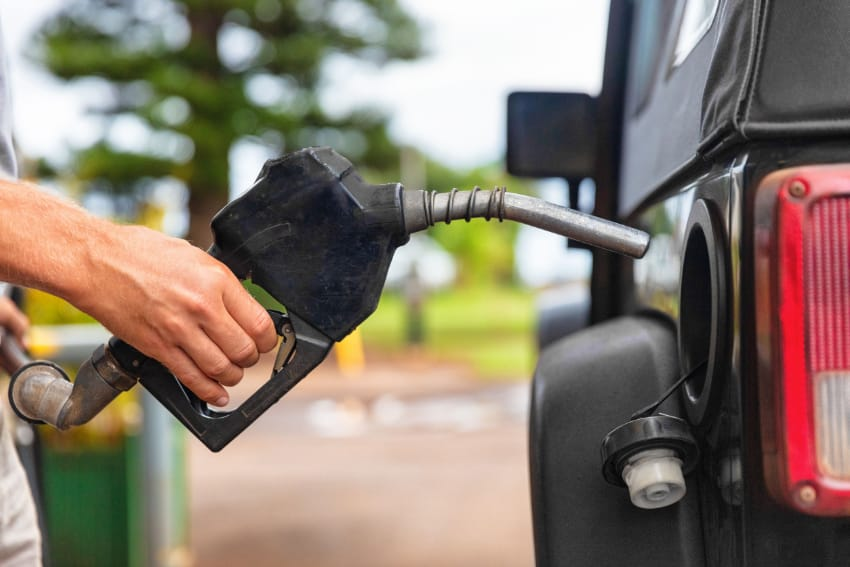 This photo is a close up of a service station attendant about to pump fuel into a car gas tank.